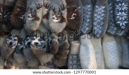Mittens on the winter Christmas market. Multi-colored knitted woolen mittens. #1297770001