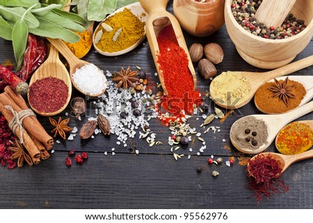 mix aromatic spices on spoons in black wooden background