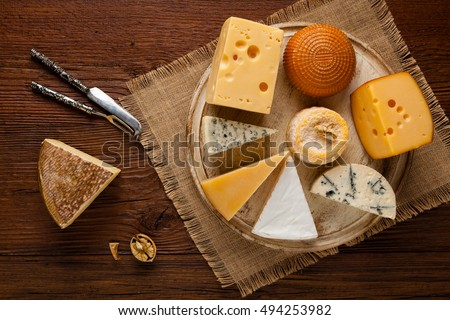 Mix cheese on wooden board with grapes. Top view.