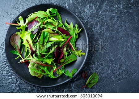 Mix fresh leaves of arugula, lettuce, spinach, beets for salad on a dark stone background. Selective focus.