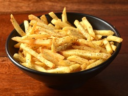 Mix herb French fries, served in a plate over a rustic wooden background, indian cusine, selective focus