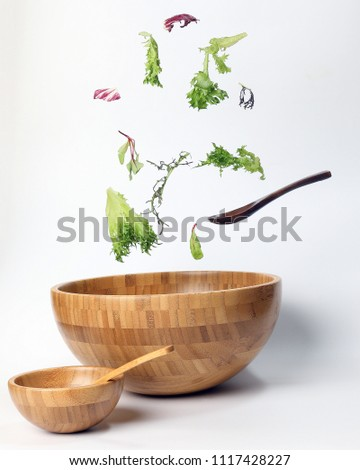 Mix leafy vegetable salad green purple lettuce glass bowl elevated flying dropping  #1117428227