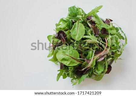 Mix lettuce leaves in a gray plate on a light background. Leaves of radishes, beets, lettuce, arugula, spinach. Vegan, healthy eating, antioxidant, detox, diet.  Copy space, top view.  Сток-фото ©