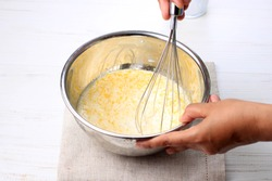 Mix Milk with Melted Butter and Egg using Baloon WHisk on Stainless Bowl