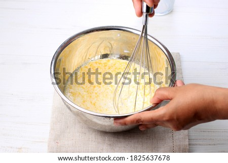 Mix Milk with Melted Butter and Egg using Baloon WHisk on Stainless Bowl  Foto stock ©