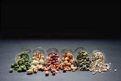 Mix Nut in the glass on black background , close up , peanut; Peas; Sunflower seeds; Pumpkin seeds; cashew nuts; pistachios