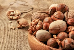 Mix nuts in a bowl, on a wooden table. Walnut, hazelnuts, macadamia, Brazil nuts or pecans. Recommended for use in anticholesterol diets