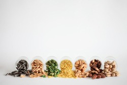 Mix Nuts in the glass on white background close up nuts pistachios  almond cashew nuts peanut sunflower seeds with copyspace