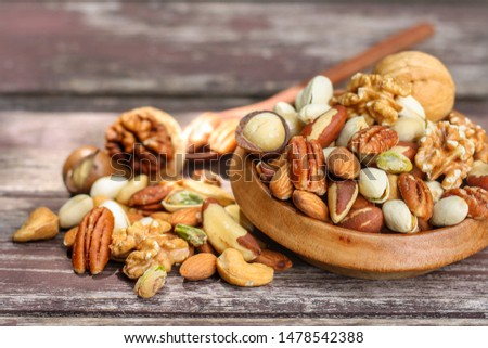 Mix nuts in wooden plate on rustic wood background.Nuts including Cashew,hazelnuts,walnuts,almonds, brazilian nuts,pecan and macadamia.Intake a handful of nut a day can stave off various disease.