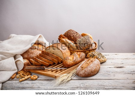 Mix of bread on cutting board and on basket