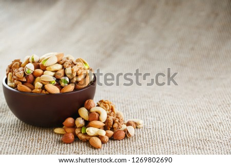 Mix of different nuts in a wooden cup against the background of fabric from burlap. Nuts as structure and background, macro. Top view. #1269802690