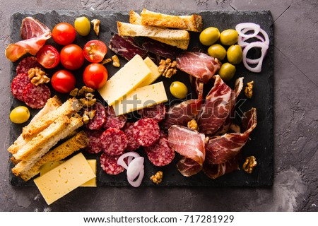 Shutterstock Mix of different snacks and appetizers. Spanish tapas on a black stone plate. Tapas bar. Sandwiches, olives, sausage,  cheese, jamon,, tomatoes, canapes. Top view