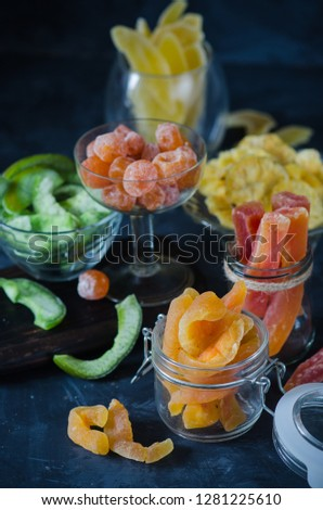 Mix of dried and sun-dried fruits, dried fruits in a glass jars and wooden plates on a black wooden background.