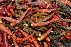 Mix of dried chili peppers. Different hot peppers varieties. Variety of shapes and colors.