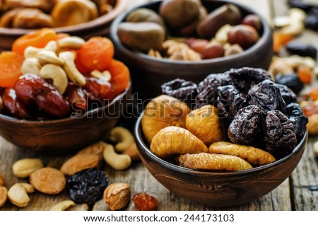 mix of dried fruits and nuts on a dark wood background. tinting. selective focus #244173103