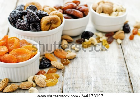 mix of dried fruits and nuts on a white wood background. tinting. selective focus #244173097