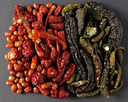 Mix of dried red and green chili peppers rectangular shape at dark background. Different hot peppers varieties.