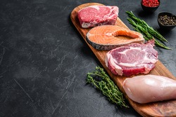 Mix of meat raw steaks salmon, beef, pork and chicken. Black background. Top view. Copy space