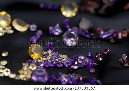 Mix of natural and colorful gems on the black background