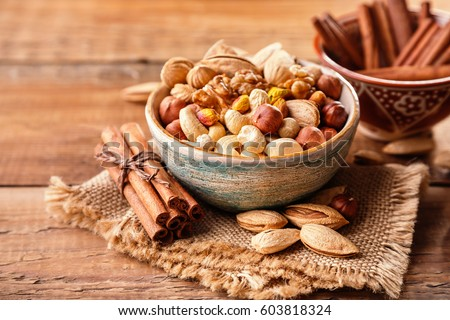 Mix of nuts and cinnamon on a old rustic table. #603818324