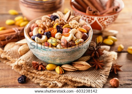 Mix of nuts and dried fruits on a old rustic table. #603238142