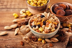 Mix of nuts and dried fruits on a old rustic table. Gold pistachios, cashews, hazelnuts, almonds.