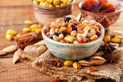 Mix of nuts and dried fruits on a old rustic table. Gold pistachios, cashews, hazelnuts, almonds. Food background.