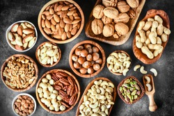 Mix of nuts in wooden bowls on dark stone table top view. Walnuts, cashew, almond, pistachio, pecan, hazelnut, macadamia nut. Healthy various super food selection.