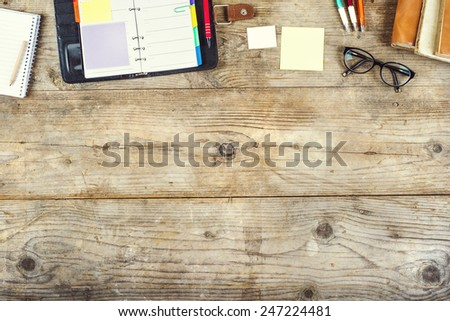 Mix of office supplies on a wooden table background. View from above.