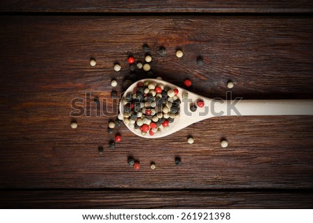 Mix of pepper seasoning in a wooden spoon close-up on the wood