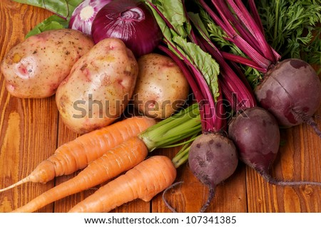 Mix of Raw Organic Farmer's Potato, Carrot, Red Onion and Beet on wooden background