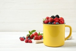Mix of ripe berries on white wooden table. Space for text