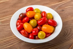 Mix of tasty multicolored cherry tomatoes in a white porcelain bowl on a brown wooden table. Vegetables, vegetarian and healthy eating. Raw food diet. Front view.