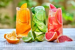 Mix of three ice refreshing drinks with orange, lime and grapefruit Cold refreshing cocktails - a healthy drink for detoxification. Summer refreshing drink. Cold water for detoxification