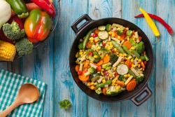 Mix of vegetables fried in a wok. Top view.