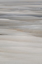 Mix of water and sand creating beautiful patterns in the Baie de Somme, Normandie, France.