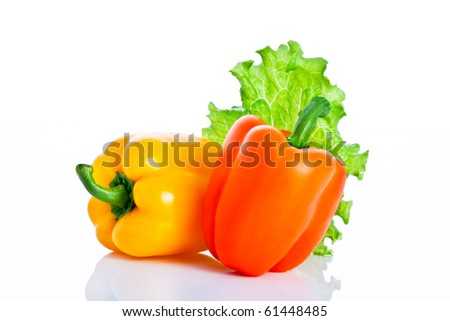 Mix of yellow and orange paprika decorated with salad isolated on white background with reflection