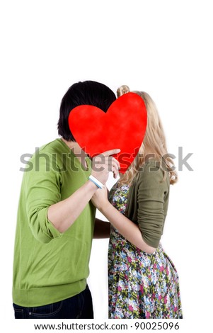 Mix race couple kissing while hiding behind a red heart