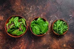 Mix Salad leafs, Arugula, Spinach and swiis Chard in wooden bowls. Dark background. Top view