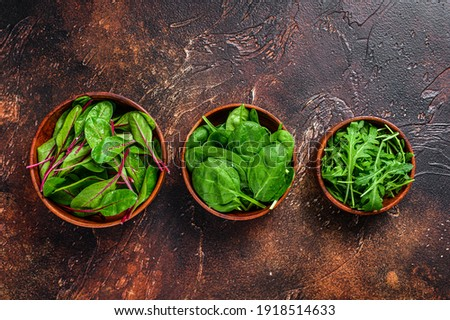 Mix Salad leafs, Arugula, Spinach and swiis Chard in wooden bowls. Dark background. Top view Foto stock ©