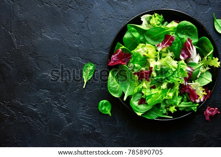 Mix salad leaves in a black bowl over dark slate, stone or concrete background.Top view with copy space. #785890705