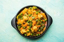 Mix vegetable curry - Indian main course recipe contains Carrots, cauliflower, green peas and beans, baby corn, capsicum and paneer/cottage cheese with traditional masala and curry, selective focus