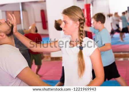Mixed age group at self protection workout, training attack movements in pairs #1221969943