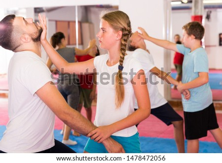 Mixed age group at self protection workout, training attack movements in pairs #1478472056