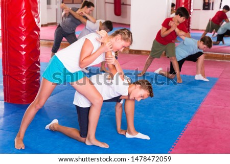 Mixed age group at self protection workout, training attack movements in pairs #1478472059