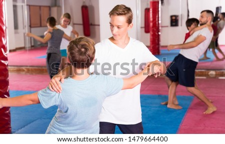Mixed age group at self protection workout, training attack movements in pairs #1479664400