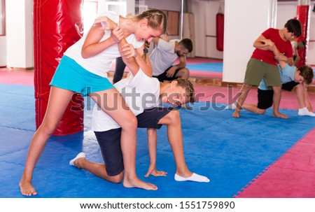 Mixed age group at self protection workout, training attack movements in pairs #1551759890