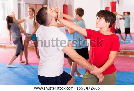 Mixed age group at self protection workout, training attack movements in pairs #1553472665