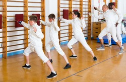 Mixed age group of athletes at fencing workout, training attack movements on mannequins