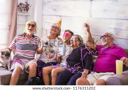 Mixed ages caucasian family at home celebrating an event or party together having a lot of fun. laughs and smiles for happy senior adult and young teenager people in friendship. Happiness and joy #1176315202